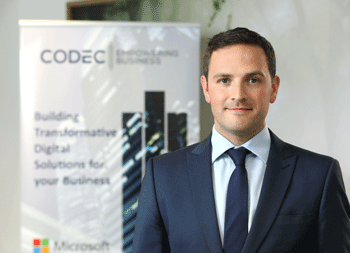 A man is displayed in the front wearing a blue suit and a blue tie. A banner with the content Codec Building Transformative Digital Solutions for your Business is displayed in the background